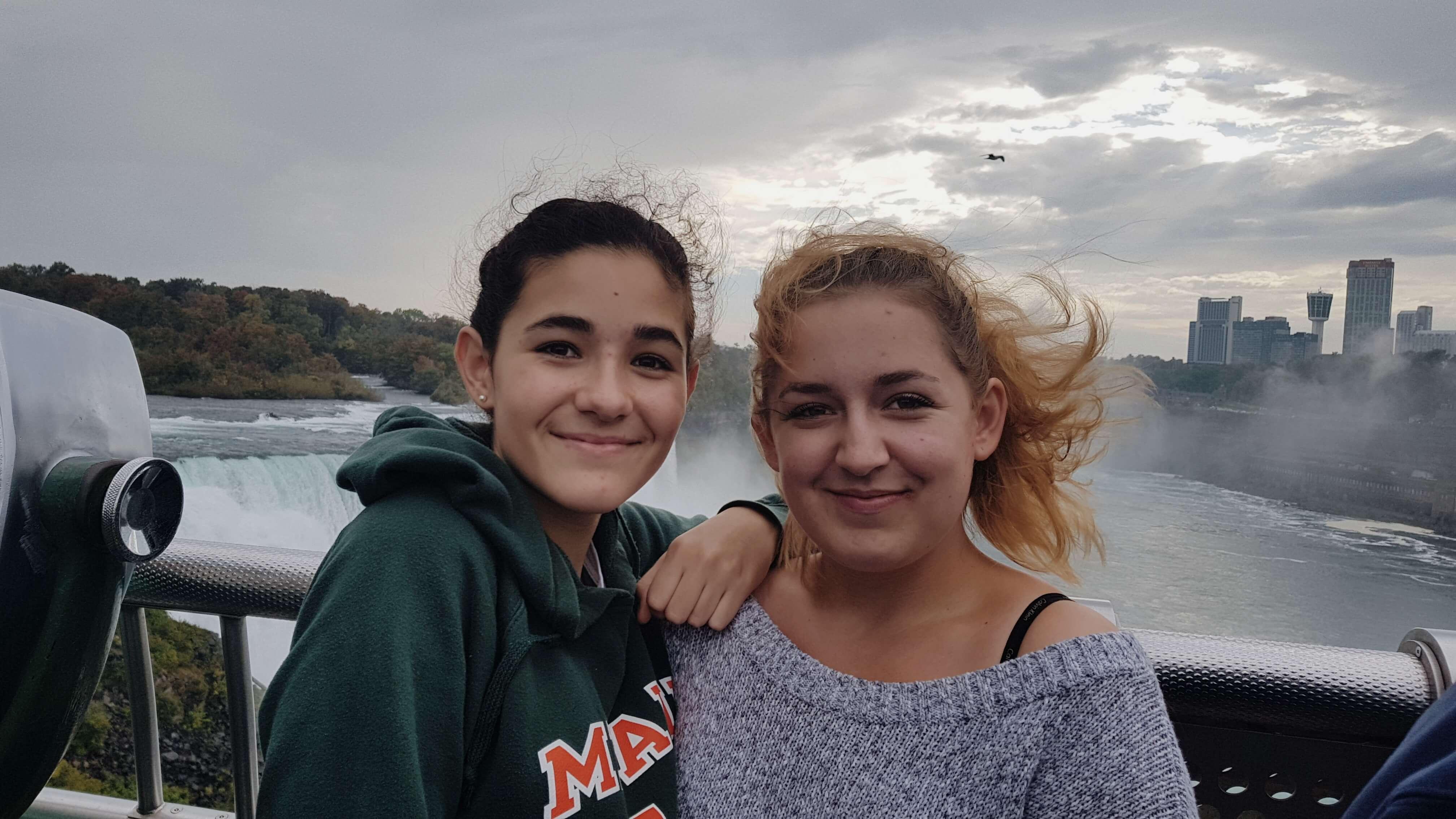 zwei lächelnde Mädchen vor den Niagara Fällen