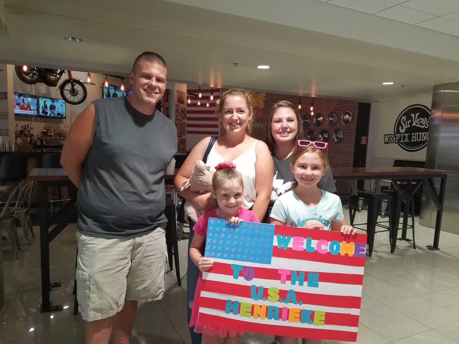 Familie mit zwei Kindern und Gastschüler, die ein Willkommensplakat hochhalten