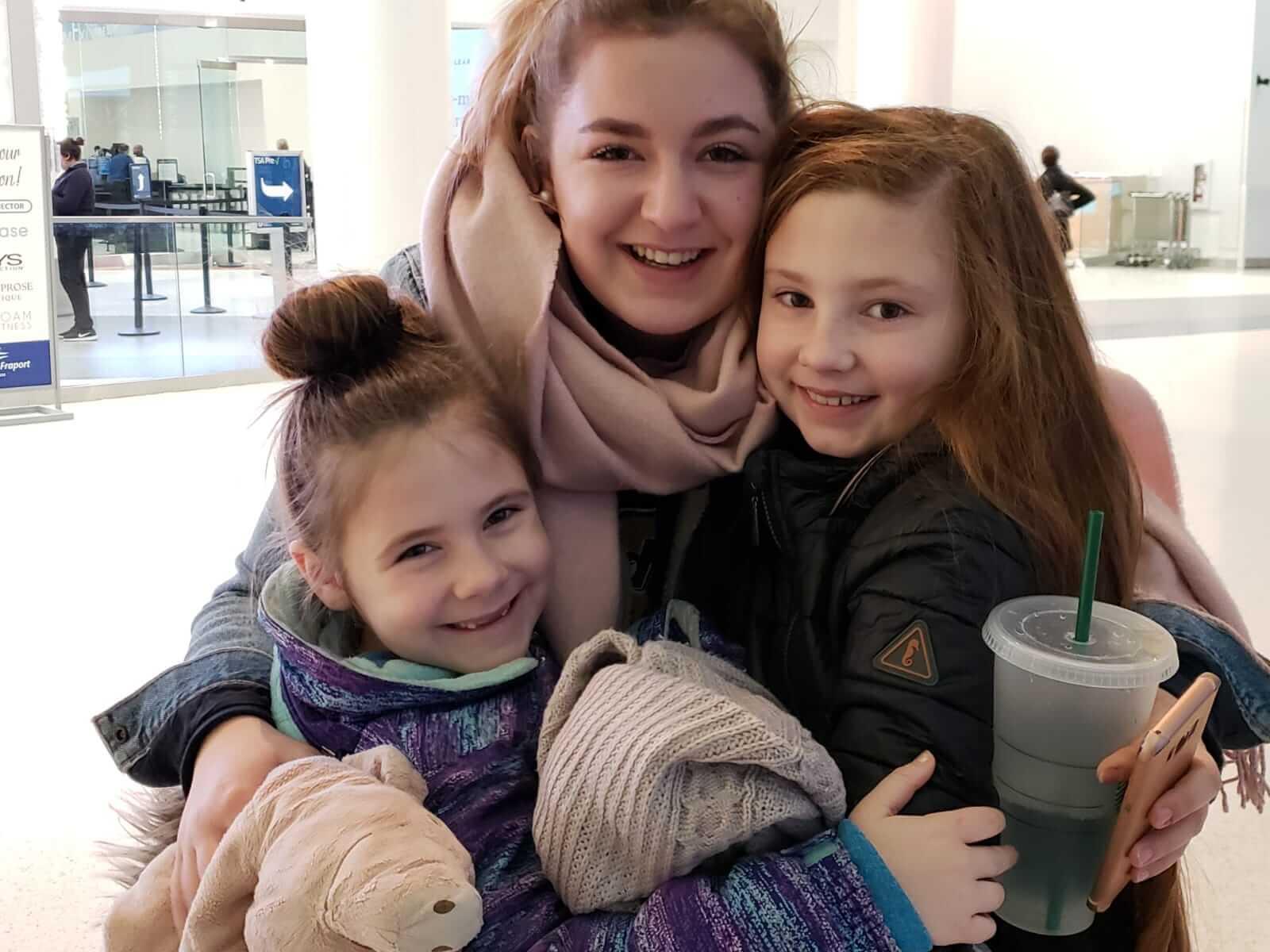 zwei kleiner Mädchen umarmen ein größeres Mädchen