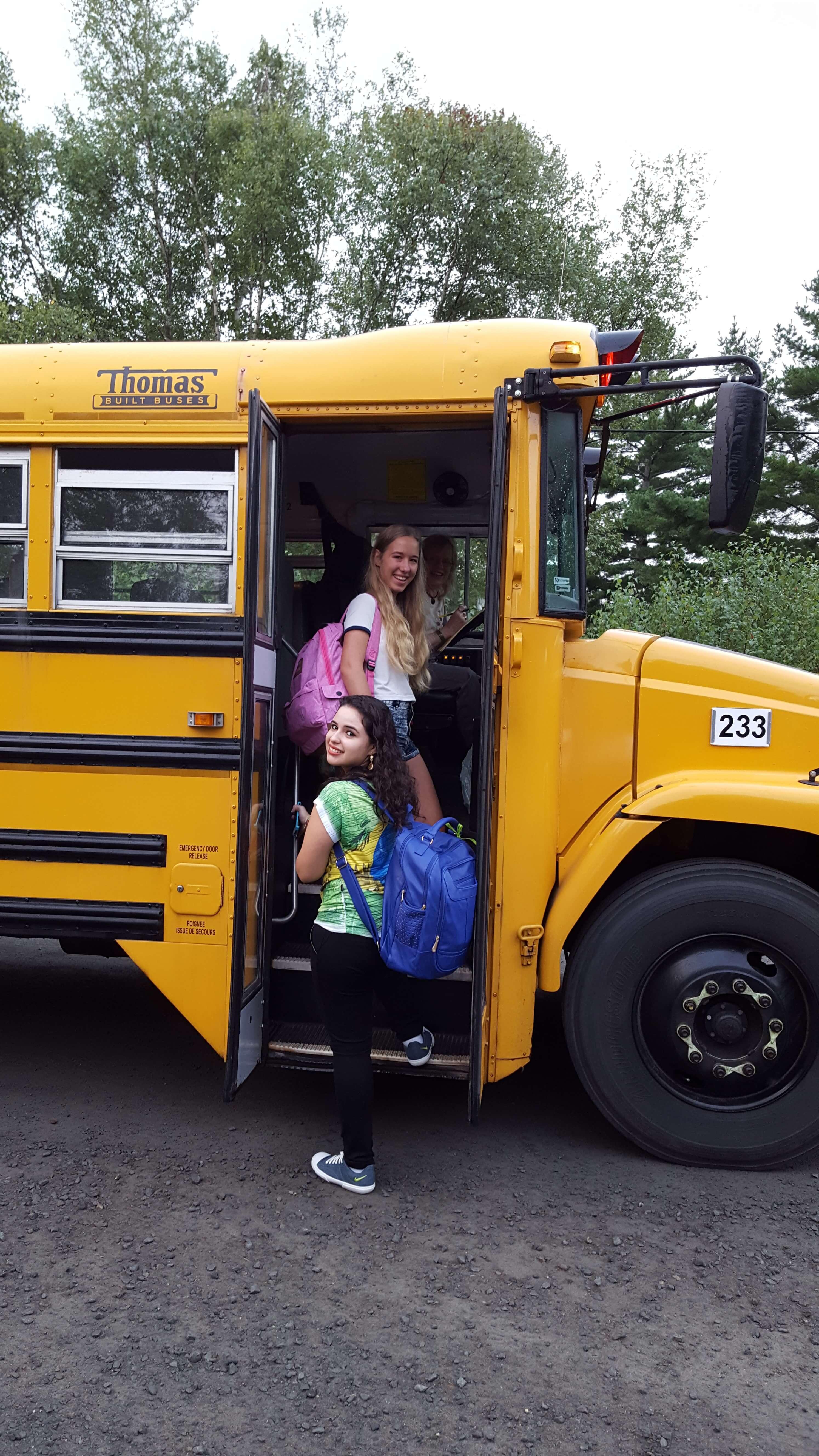 zwei Schülerinnen steigen in den typisch gelben Schulbus ein und lächeln in die Kamera
